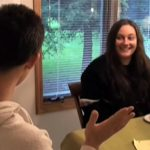 Image of a man and a woman sitting at a table. The man is speaking while the woman looks at him, smiling.